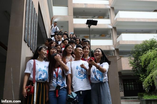 """""""安康家园""""的孩子们穿着统一的文化衫,举起手机自拍留影。"""