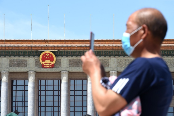"""《民法典 你的法典》十三届全国人大三次会议召开在即,民法典草案将提请审议,这事本次全国""""两会""""最受瞩目的事情之一。图为2020年5月20日,市民在北京人民大会堂前拍照。"""