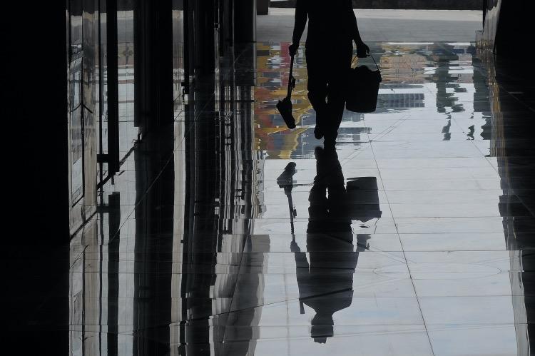 """《""""楼栋自管"""" 为何行之不远》(图文无关)从事物业管理工作的保洁员在瓷砖地面上留下倒影。"""