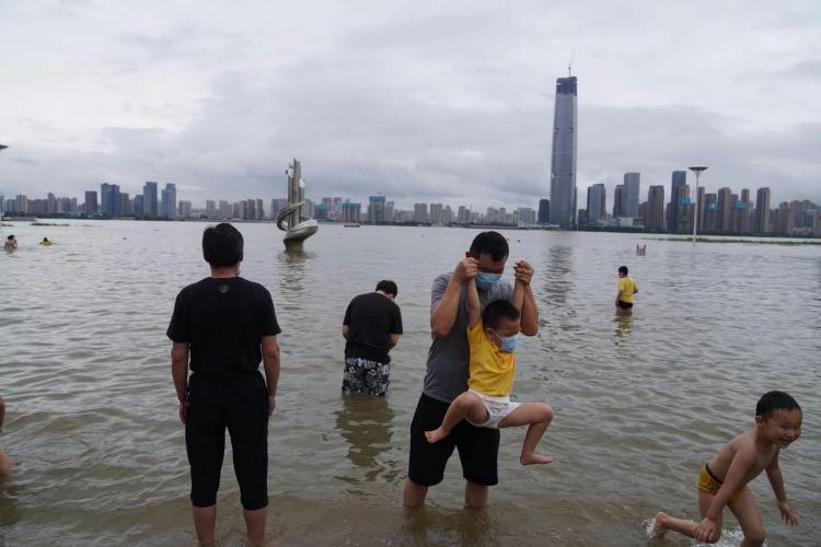 帶小孩的市民在江水里玩耍。(2)