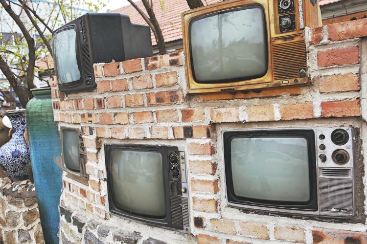 《小城故事 | 刚有电视时, 我们追过的那些剧》(图文无关)那时候,刚有电视。当时的电视机笨头笨脑、巨厚巨沉。一个十四寸电视机,需要两个成人合力才搬得动。图为一处创意园区里,五台不同品牌的黑白电视机镶嵌在砖墙里。