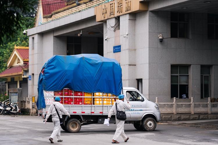 """2020年9月11日,云南德宏瑞丽,为保障中缅两国贸易的进行,瑞丽国门的货运依旧畅通。遵照""""人货分离、分段运输、封闭管理""""的政策,缅甸货车在国门处由身穿防护服的中国司机开进中国境内货场。"""