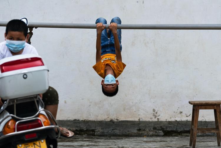 瑞丽市一社区内,小朋友边玩耍边等待核酸检测人员的到来。