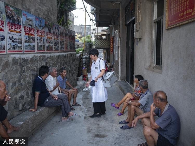 王锦萍在出诊时和正在乘凉的村民们攀谈。