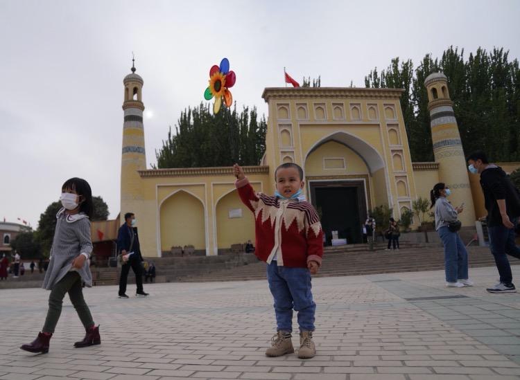 一名小男孩舉著風車,在艾提尕爾廣場上拍照。