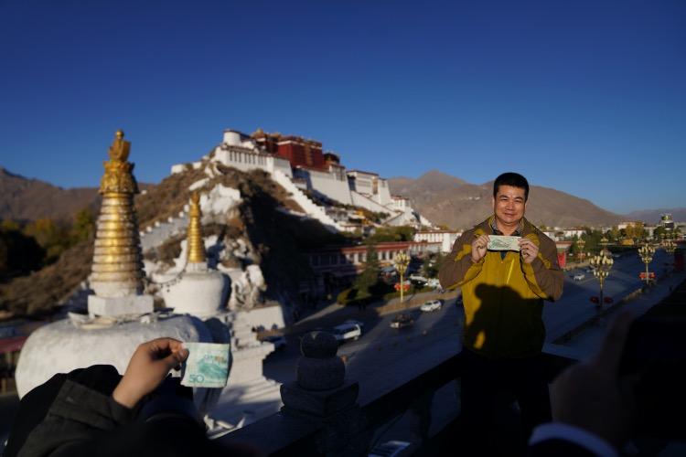 一名游客站在药王山观景台背对着布达拉宫,将人民币纸币50元拿在手上,纸币上印有布达拉宫的图案。