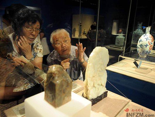 7月29日,观众在首都博物馆欣赏故宫博物院藏的玉雕。