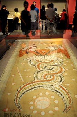 7月29日,观众在首都博物馆欣赏新疆维吾尔自治区博物馆藏的伏羲女娲图绢画。
