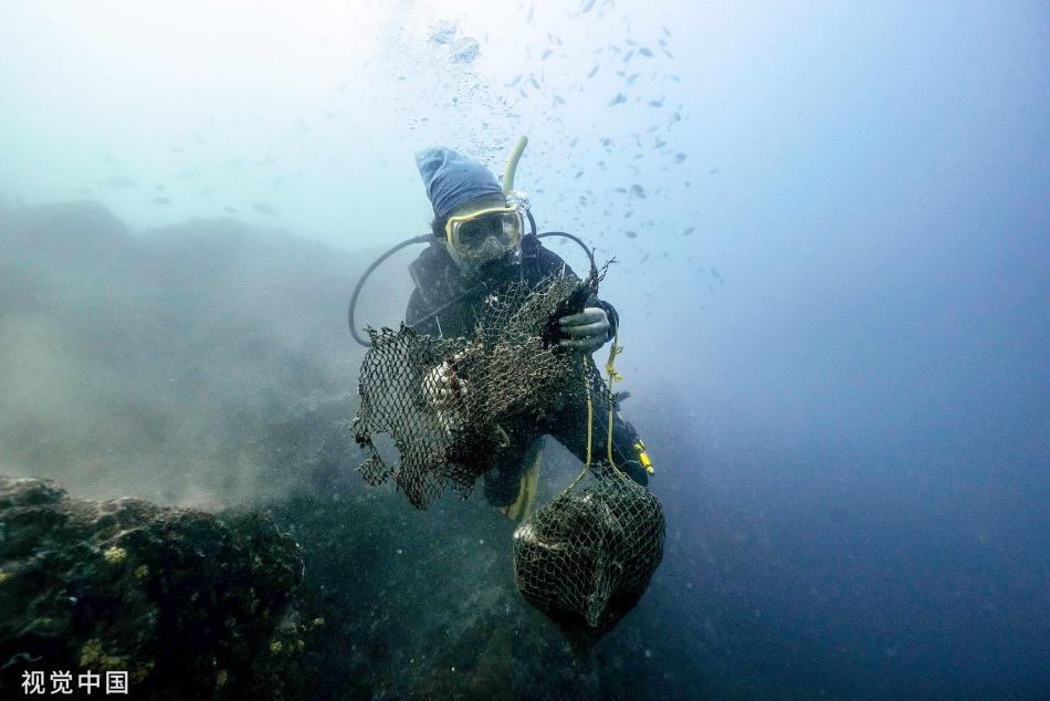 在春武里府(Chonburi)海岸,潜水员剪断缠绕在礁石上的废弃渔网,并将它们收集上岸。