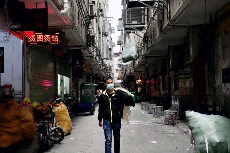 一位制衣廠老板拿著服裝樣板從工廠里走出。在康樂村這座城中村里,集聚著數千家制衣廠、小作坊。