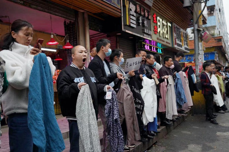 2021年3月3日,廣東廣州,元宵節之后的工作日,制衣廠的老板們排成一列,手里拿出樣板站在康樂村街頭,招募前來務工人員。