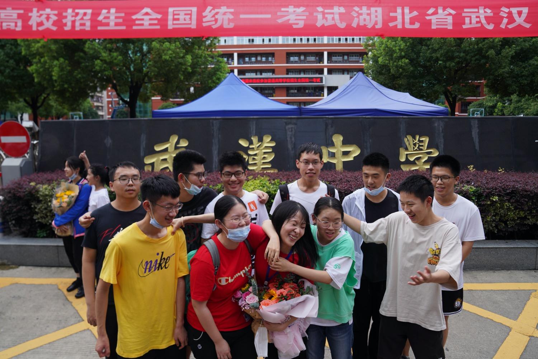 """《教育部:经过大风浪,扛过""""连环考"""" 》熬到2020年3月的最后一天,距离原定高考开考时间仅剩68天。教育部终于向社会公布了高考延期的消息。图为2020年7月8日,参加完2020年全国高考的考生在武汉中学考点外互相拥抱。"""