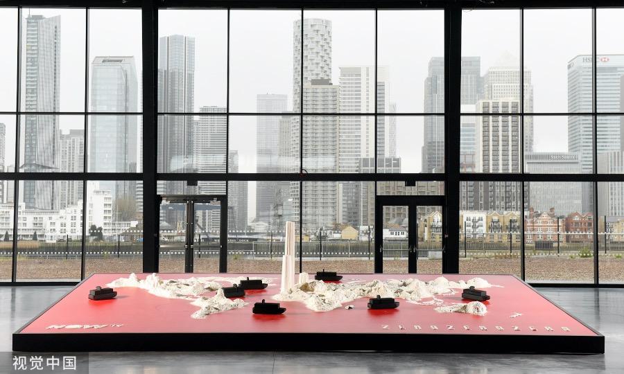藝術品陳列在倫敦的格林尼治區,透過玻璃窗仿佛正在凝視著市區里座座高聳的摩天大樓。