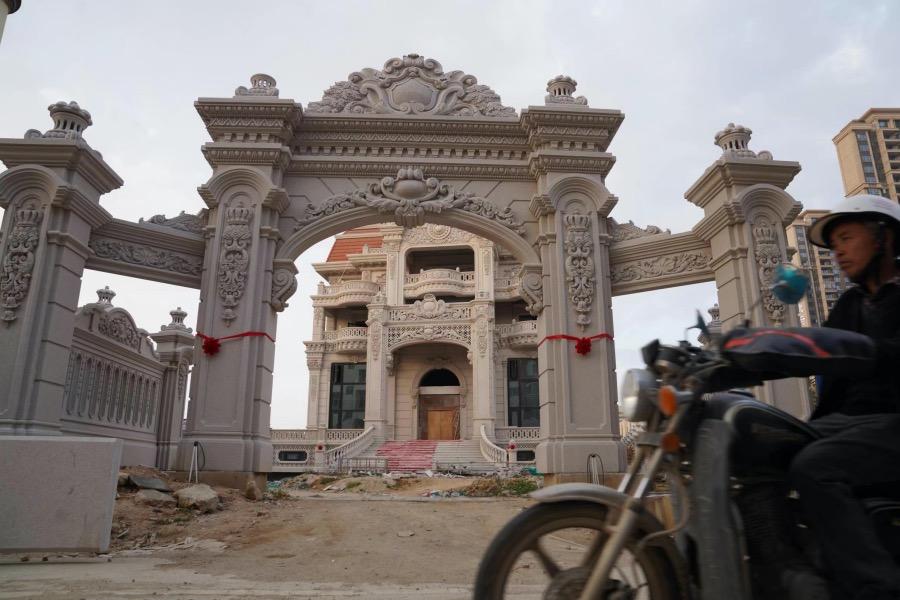 一位当地人骑摩托车在一个在建豪宅前经过,这个雕花工艺复杂的欧式大门花费大约八百万元。