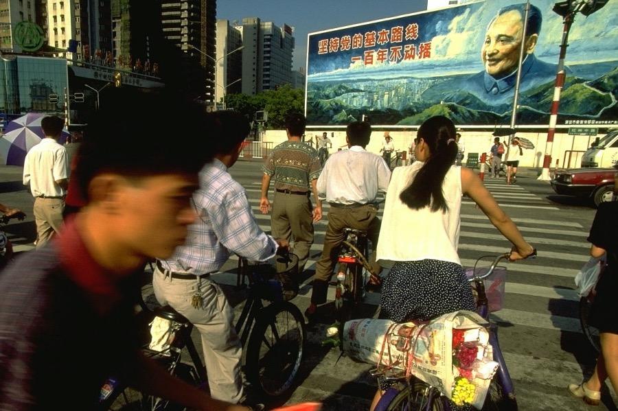 """《""""春天通訊員""""吳松營:""""當時知道他來,大家真的高興""""》1993年,中國深圳,鄧小平畫像下的繁忙路口。"""