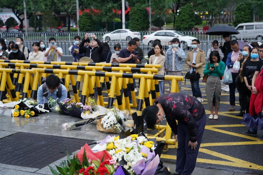 2021年5月22日下午,在長沙湘雅醫院大門外獻花的市民向著花束鞠躬。3