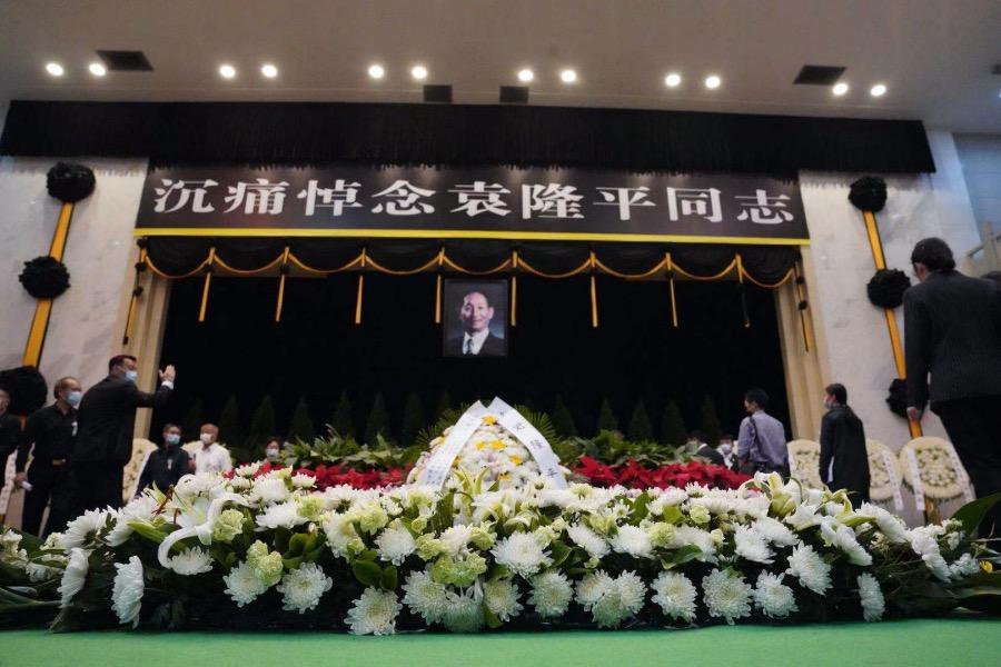 """銘德廳正廳上方懸掛著黑底白字的橫幅""""沉痛悼念袁隆平同志"""",橫幅下方是袁隆平同志的遺像。"""
