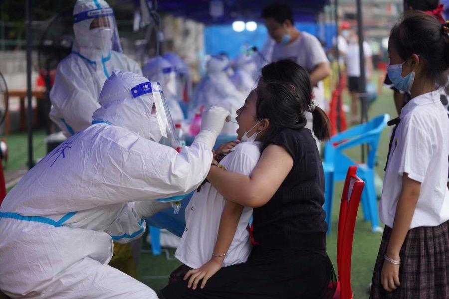 2021年5月30日,海珠区凤阳街道,一位妈妈抱着自己的孩子在接受核酸检测。