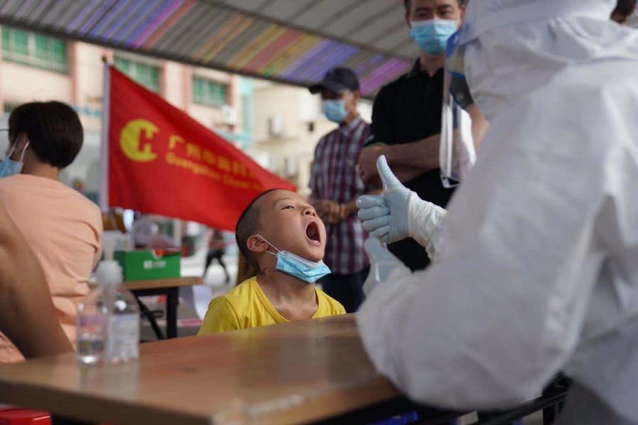 2021年5月30日,越秀区北京路,医护人员给刚刚做完咽拭子采集的小朋友竖起拇指点赞。