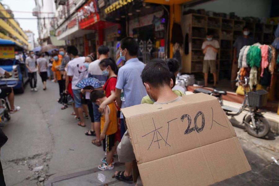 """2021年5月30日,海珠区凤阳街道,有人身披一片纸皮写着""""本厂20人"""",替工厂的工人们排队。"""