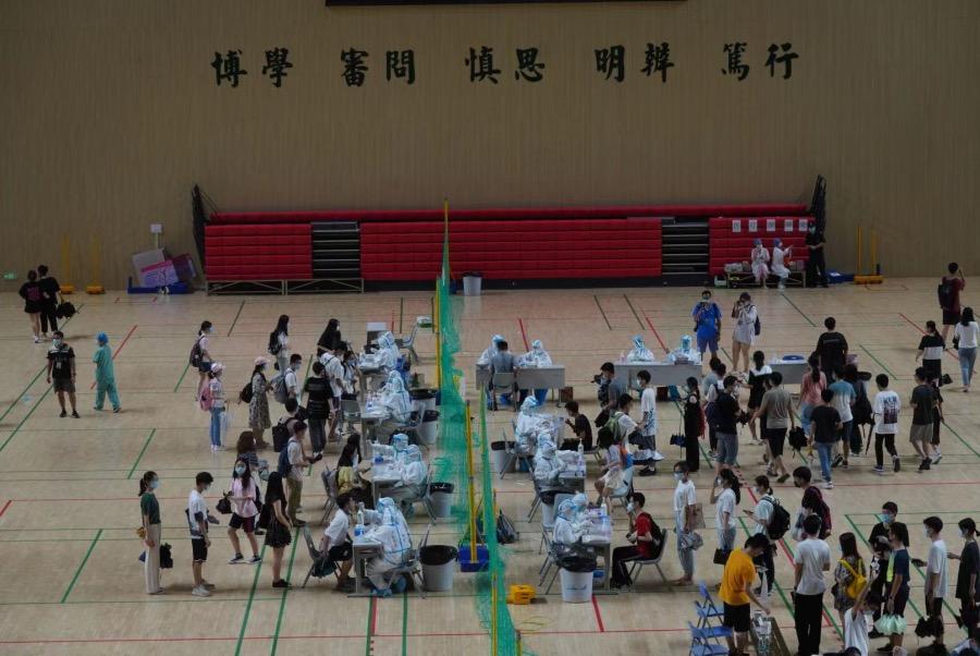 2021年5月30日,中山大学南校区体育馆墙上悬挂着中大校训,学生们排着队等候进行核酸采集。