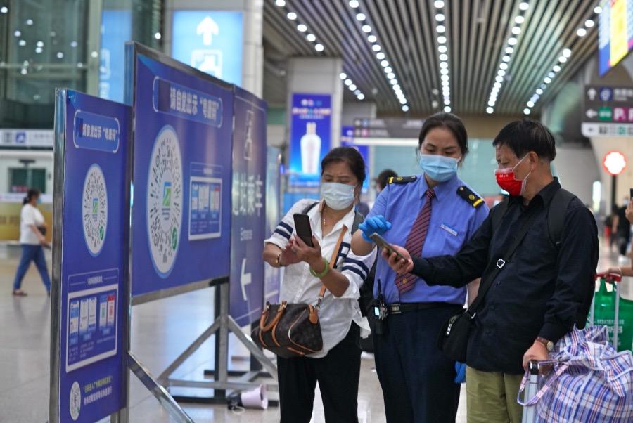 """2021年5月31日晚上,广州南站的旅客在铁路部门工作人员的指引下登陆""""健康码""""以备进站查验。"""