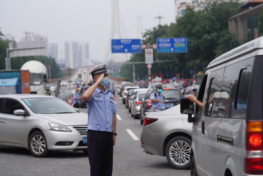 2021年6月24日,廣東廣州,鶴洞大橋鶴洞路上橋位置,交警在指揮交通。一位司機把手伸出車窗向一位執勤交警比贊,交警敬禮回應。