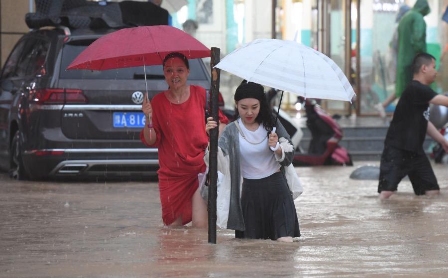 2021年7月20日,河南郑州的强降雨天气造成城区内部分路段积水,给市民出行带来不便,能扶拄的木棍成了涉水利器。