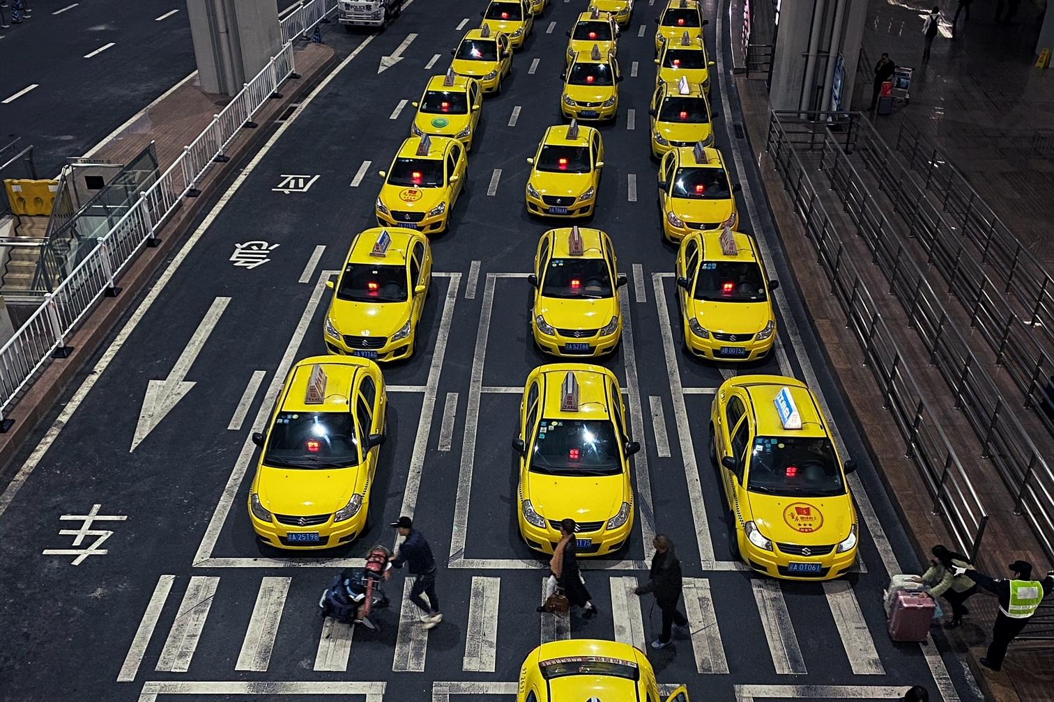 《电动汽车往事:诞生更早, 却被后起的内燃机汽车淘汰》归根结底,如果电池技术没有革命性突破,电动汽车恐怕行之不远。图为重庆机场外排队等候客人的燃油出租车。